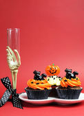 Happy Halloween party food with skeleton hand glass on red background, with cupcakes — Stock Photo