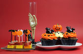 Happy Halloween party food, cupcakes and cocktail bites, with skeleton hand glass — Stock Photo