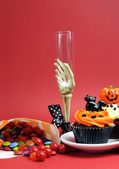 Happy Halloween party food with skeleton hand glass on red background, with cupcakes and candy lollies. — Stock Photo
