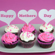 Happy Mother's Day message across white heart toppers on pink and white decorated red velvet cupcakes — Stock Photo #24018295