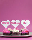 Happy Mother's Day message across white heart toppers on pink and white decorated red velvet cupcakes on pink background. Vertical with copy space for your text here. — Stock Photo