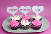 Happy Mother's Day message across white heart toppers on pink and white decorated red velvet cupcakes — Stock Photo