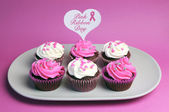 Pink Ribbon Day message across white heart toppers on pink and white decorated red velvet cupcakes — Stock Photo