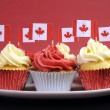 Red and White cupcakes with Canadian maple leaf national flags against a red background for Canada Day or Canadian national holidays. — Stock Photo