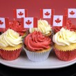 Red and White cupcakes with Canadian maple leaf national flags against a red background for Canada Day or Canadian national holidays. Close-up. — Stock Photo