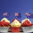 Australian theme red, white and blue cupcakes with national flag for Australia Day, Anzac Day or national holiday against a blue background. Vertical with copy space. — Stock Photo #24421553