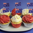 Australian theme red, white and blue cupcakes with national flag for Australia Day, Anzac Day or national holiday against a blue background. Close-up. — Stock Photo #24421571