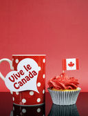Red and white theme Canadian cupcake with maple leaf flag and red polka dot coffe mug with Happy Canada Day, Vive Le Canada, or copy space for your text here. Vertical with copy space. — Stock Photo