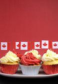 Cupcakes rosso e bianco con bandiere nazionali di foglia d'acero canadese contro uno sfondo rosso per il giorno della festa o festività nazionali canadesi. verticale con spazio copia per il tuo testo qui. — Foto Stock