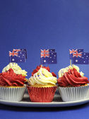 Australian theme red, white and blue cupcakes with national flag for Australia Day, Anzac Day or national holiday against a blue background. Vertical with copy space. — Stock Photo