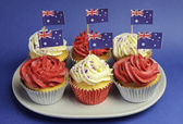 Australian theme red, white and blue cupcakes with national flag for Australia Day, Anzac Day or national holiday against a blue background. Close-up. — Stock Photo