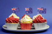 Australian theme red, white and blue cupcakes with national flag for Australia Day, Anzac Day or national holiday against a blue background. — Stock Photo