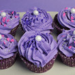 Mauve purple decorated cupcakes for children or teens birthday, or bachelorette, bridal or baby shower party function - aerial view. - Stock Photo