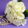 Wedding bouquet of white roses with string of pearls necklace and heart sign  against purple lilac background. — Stock Photo