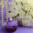 Wedding bouquet of white roses with purple cupcake and pearls in champagne glass, against purple lilac background. Close up with bokeh. — Stock Photo