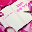 Happy New Year resolutions in diary journal book with pretty feminine pink ribbons - Stock Photo