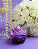 Wedding bouquet of white roses with purple cupcake and pearls in champagne glass, against purple lilac background. Vertical close up — Foto de Stock