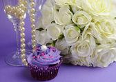紫のカップケーキとシャンパン グラス、紫色のライラックを背景に真珠白バラの結婚式の花束。ボケ味とクローズ アップ. — ストック写真