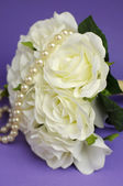 Wedding bouquet of white roses with string of pearls necklace. Vertical close up with bokeh — Stock Photo