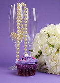 Wedding bouquet of white roses with purple cupcake and pearls in champagne glass, against purple lilac background. Vertical. — Stock Photo