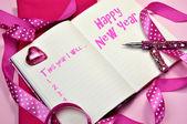 Günlük günlüğü kitap oldukça kadınsı pembe kurdeleler ile mutlu yeni yıl kararları — Stok fotoğraf