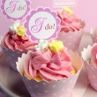 Pink wedding cupcakes with I Do topper signs - close up with bokeh vertical. — Stock Photo
