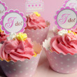 Stock Photo: Pink wedding cupcakes with I Do topper signs on pink cake stand - close up.