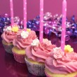 Pink birthday cupcakes with polka dot candles against a pink background. Vertical with shallow focus on second cupcake. — Stock Photo