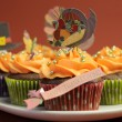 Happy Thanksgiving cupcakes with turkey, feast, and pilgrim hat topper decorations against a harvest red brown background. Close up with shallow DOF bokeh. - Stock Photo