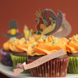 Happy Thanksgiving cupcakes with turkey, feast, and pilgrim hat topper decorations against a harvest red brown background. Close up with bokeh vertical, with copy space. — Stock Photo #25422957