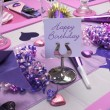 Pink and purple theme party table setting decorations with Happy Birthday message on table stand. — Stock Photo #25423059