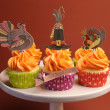 Happy Thanksgiving decorated cupcakes with turkey, pilgrim hat and corn toppers on cake stand against a brown background. — Стоковая фотография