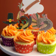 Happy Thanksgiving decorated cupcakes with turkey, pilgrim hat and corn toppers on cake stand against a brown background. — Stock Photo #25423387