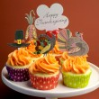 Happy Thanksgiving decorated cupcakes with turkey, pilgrim hat and corn toppers on cake stand against a brown background, with Happy Thanksgiving message. — Stock Photo
