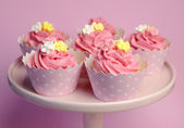 Beautiful pink decorated cupcakes on pink cake stand for birthday, wedding or female special event occasion, with pink, yellow and white fondant roses and pink star cups. — Stock Photo