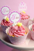 Pink wedding cupcakes with I Do topper signs - close up with bokeh vertical. — Foto Stock