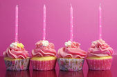 Pink birthday cupcakes with polka dot candles against a pink background. — Stock Photo