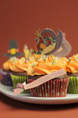 Happy Thanksgiving cupcakes with turkey, feast, and pilgrim hat topper decorations against a harvest red brown background. Close up with bokeh vertical, with copy space. — Stock Photo