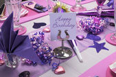 Pink and purple theme party table setting decorations with Happy Birthday message on table stand. — Stock Photo