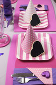 Pink and purple theme party table setting decorations. Vertical with party hats and pink strip plates. — Stock Photo