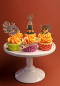 Happy Thanksgiving decorated cupcakes with turkey, pilgrim hat and corn toppers on cake stand against a brown background. Vertical — Stock Photo