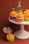 Happy Thanksgiving decorated cupcakes with turkey, pilgrim hat and corn toppers on cake stand against a brown background. Vertical with extra cupcake on table. — Stock Photo