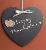 Happy Thanksgiving message written on heart shape blackboard with turkey motif decoration. — Stock Photo
