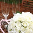 Wedding bridal bouquet of white roses with two champagne glasses with pink polka dot ribbon on outdoor garden table setting after rain. Vertical. — Stock Photo