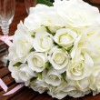 Wedding bridal bouquet of white roses with two champagne glasses with pink polka dot ribbon on outdoor garden table setting after rain. Close up. — Stock Photo