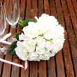 Wedding bridal bouquet of white roses with two champagne glasses with pink polka dot ribbon on outdoor garden table setting after rain. Horizontal with copy space. — Stock Photo