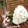Wedding bridal bouquet of white roses with two champagne glasses with pink polka dot ribbon on outdoor garden table setting after rain. — Stock Photo