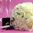 Wedding bridal bouquet of white roses on pink background with pair of champagne flute glasses and gold wedding ring in black jewelry box. — Stock Photo