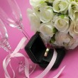 Wedding bridal bouquet of white roses on pink background with pair of champagne flute glasses and gold wedding ring in black jewelry box. - Stock Photo