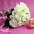Wedding bridal bouquet of white roses on pink background with pink cupcake and pair of two champagne flute glasses. — Stock Photo